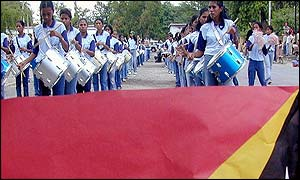 Band marches behind Timorese flag