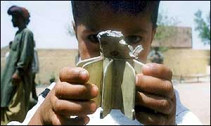 Boy in Indian Kashmir displays the tail of a Pakistani mortar bomb