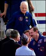 [ image: John Glenn emerges from a crew transport vehicle - in high spirits]