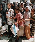 [ image: Children in Baghdad queue for food donations outside a mosque]