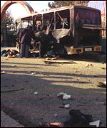 [ image: Police examine the remains of the bus]