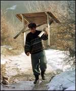 [ image: An Albanian carries a table to the hills - many are hiding in the woods]