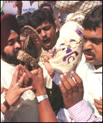[ image: Protesters demanding Thackeray's arrest attack an effigy of India's home minister]