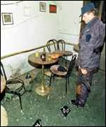 [ image: A Serb policeman inspects the damage in a Pristina cafe after a bomb went off]