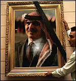 [ image: Black ribbons adorn pictures of King Hussein]