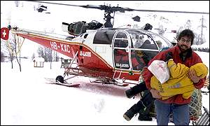 [ image: A tourist carries his daughter from a helicopter after being airlifted to safety]