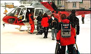 [ image: Tourists board a helicopter to be airlifted out of the alpine village of Elm]