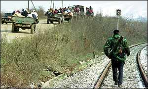 [ image: Refugees ride past a Kosovo Liberation Army soldier]