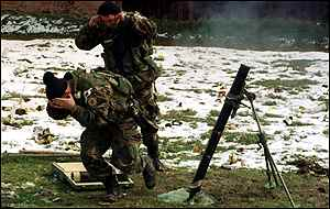 [ image: Yugoslav army soldiers fire on the attack in Drenica, central Kosovo]
