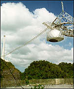 [ image: The detector antenna at Arecibo hangs over the dish]