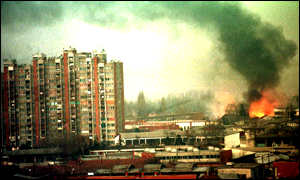 [ image: The aftermath:  Smoke rises from civilian buildings near the largest military barracks in Pristina on Thursday morning]