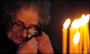 [ image: An elderly Serbian woman cries after the overnight raid as she lights candles in St Mark's Orthodox Church, Belgrade]