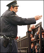 [ image: Refugees clamour at the gates as the Macedonian police check documents]