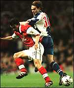 [ image: Blackburn's McAteer (right) tussles with Overmars for the ball]