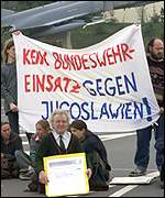 [ image: Demonstrators protest against German involvement]