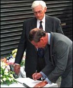 [ image: Seamus Mallon watches as Prince Charles signs a book of condolence after the Omagh bombing]