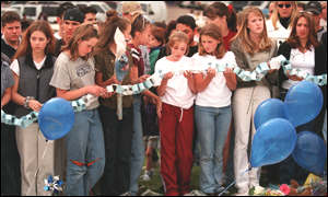 [ image: Students hold a prayer chain outside the school]