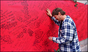[ image: Messages on a giant card convey the scale of loss]