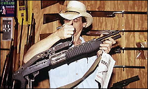 A man holds a rifle in a gun shop