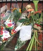 [ image: Floral tributes in memory of Dando]