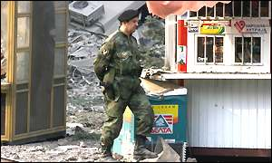 [ image: The morning after: A soldier patrols outside the bombed army HQ]
