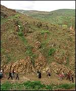 [ image: Refugees are guided along mountain trails]