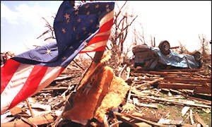 [ image: A US flag flutters amid the rubble]