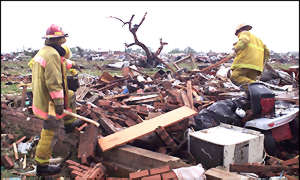 [ image: Firefighters examine the remains of a home]
