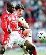 [ image: Brian Deane battles for the ball with United's Gary Neville]
