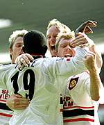 [ image: Yorke is engulfed by his team-mates after scoring the winner]
