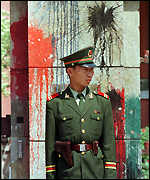[ image: A guard stands beside the splattered walls of the British embassy]