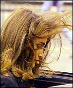 [ image: Windswept Queen Rania is accompanying her husband]