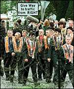 [ image: Orangemen look over to the nationalist Garvaghy Road while on their way to Drumcree]