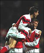 [ image: Alan Smith is hugged by Kevin Campbell and Ian Selley]