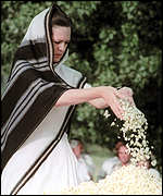 [ image: Mrs Gandhi pours flowers on the grave of her assassinated husband, Rajiv Gandhi]