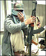 A Kashmir rebel fighter holds a rifle