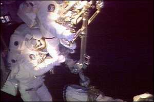 [ image: Barry, left, helps Jernigan get her feet into a restraint at the end of the shuttle's robotic arm]