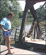 [ image: A local man examines the devastated bridge]