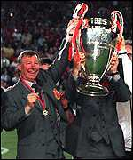 [ image: Alex Ferguson holds aloft one of the three trophies which his side won this season]