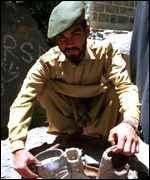 [ image: A Pakistani soldier displays shells fired by India]