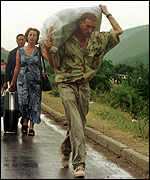 [ image: Ethnic Albanians have been carrying all that they can home]