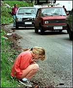 [ image: A girl at the Kosovo border watches a convoy of Serbs return]