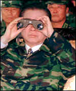 [ image: President Kim Dae-Jung looks across the border to the North]
