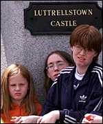 [ image: Young fans wait outside the castle grounds]
