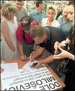 [ image: Protesters sign a petition calling for Milosevic to quit]