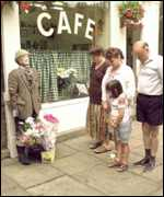 [ image: Fans lay flowers by a statue of Compo outside the famous cafe]