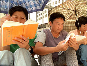 Falun Gong members consult their handbooks