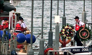 [ image: Wreaths are carried on to the USS Sanibel by coastguards]