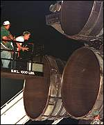 [ image: Nasa engineers inspect the engine nozzles]
