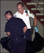 [ image: Police remove the body of one of Barton's children]